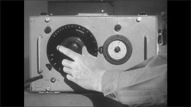1950s: Man turns knobs on signal generator.