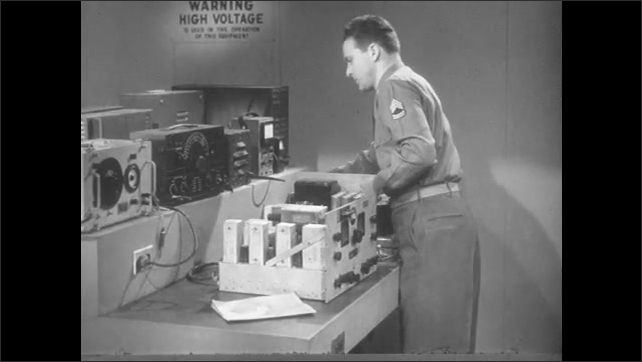 1950s: Man turns dial on electronics, gears turn inside equipment. Man hooks wires into electronics and into plug in table.