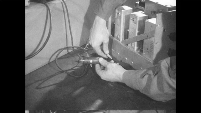1950s: Man in lab with radio equipment. Hands remove electrodes from machine part, pick up capacitor.