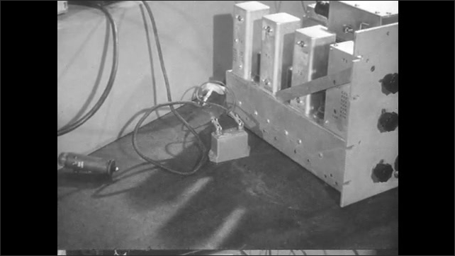 1950s: Hands clamp electrodes to capacitor.
