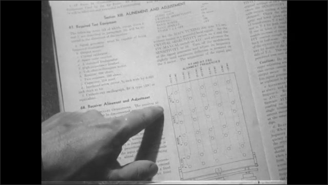 1950s: Man looks at booklet in lab. Close up, hand points to text on page. Man adjusts knobs on equipment.
