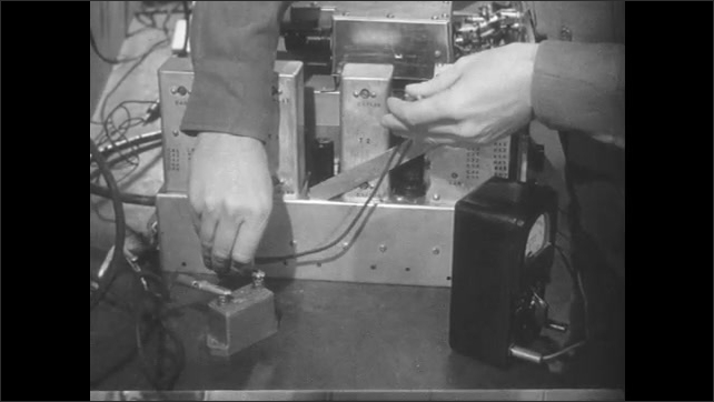 1950s: Man with equipment in lab. Hands clamp electrodes to capacitor. Man working in lab.