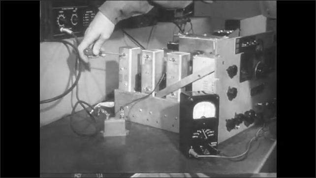 1950s: Hand adjusts screws on machine parts. Man in lab, flips over machine part.