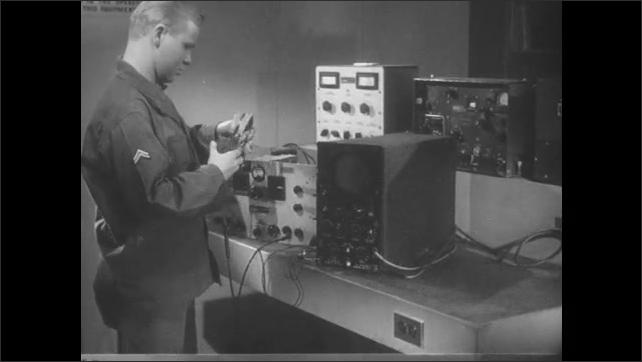 1950s: Close up, hand puts tool into machine parts. Man in lab, puts on headphones, adjusts equipment.