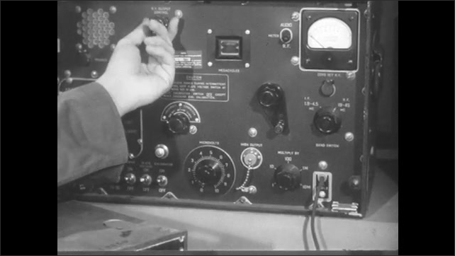 1950s: Hand adjusts knobs on machine.