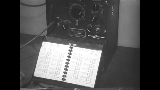 1950s: Man moves machine in lab. Hand turns page of booklet. Close up, finger points to numbers in book.
