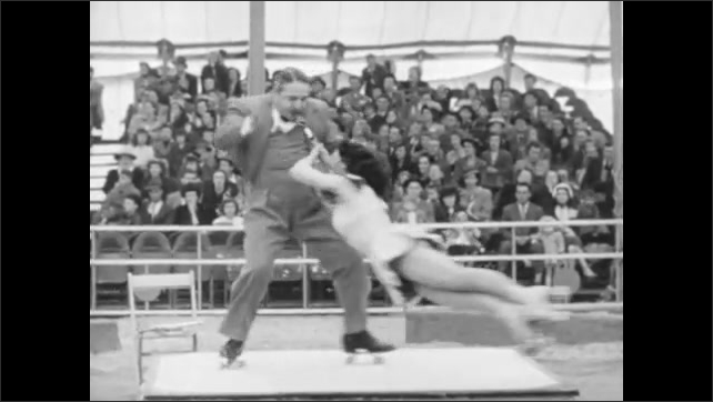 1940s: Audience claps in bleachers. Man and woman perform iron jaw roller skating act. Woman and man spin around in iron jaw act for audience.