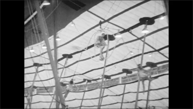 1940s: Women spin high above circus floor in iron jaw act. Acrobats leap onto see saws and perform flips.