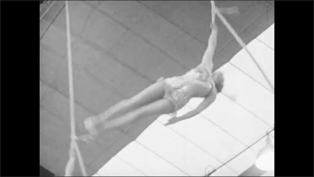 1940s: Audience claps in bleachers. Women spin on suspended ropes in aerial ballet act. Trained ponies run around circus floor near audience.