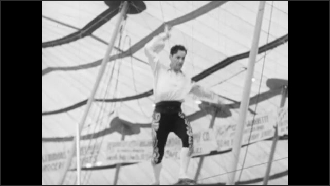 1940s: Audience claps in bleachers. Man balances and bounces on tight rope above circus floor. Man dances and flips on tight rope.