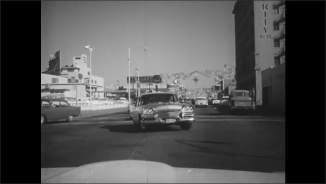 1960s: Man in truck smiles. Truck pulls past car. Traffic navigates crowded intersection.
