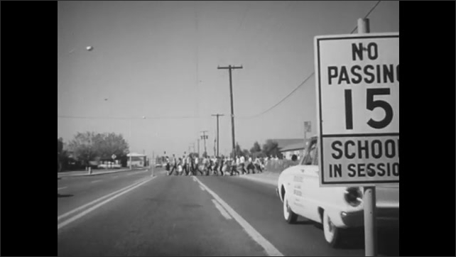 1960s: Traffic drives down busy highway past speed limit signs. Cars slow as group of pedestrians cross street. Car drives down neighborhood street.