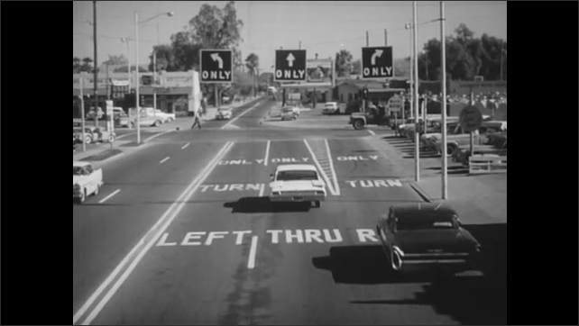 1960s: Cars pass driver in middle lane of road. Cars diverge into turn only lanes on city street.