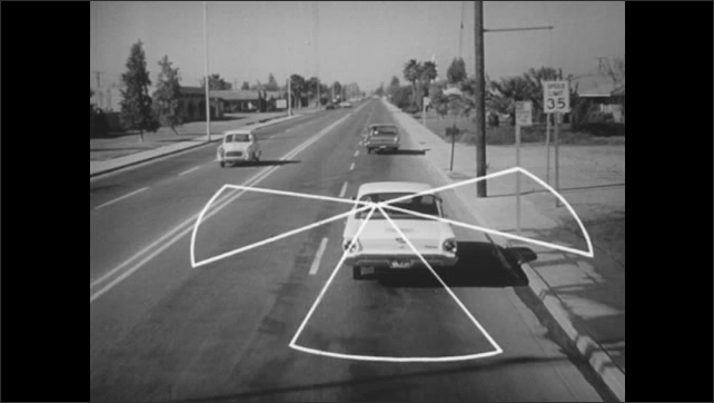 1960s: Cars drive along city highway. Illustrated letter, cones and circle appear near car. Car passes driver in left lane.