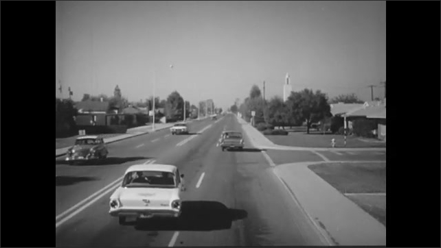 1960s: Man drives car and looks at side mirror. Car appears in side mirror.  Driver turns head and glances. Driver passes car on left. Cars drive on three lane road.