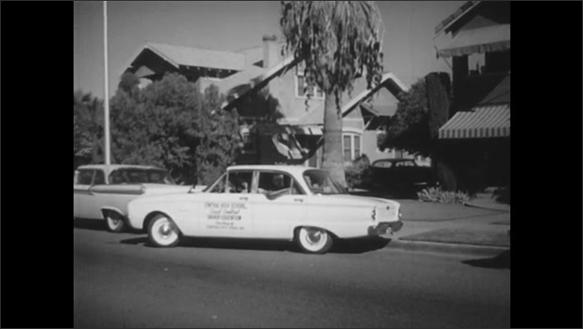1960s: Woman looks from car window. Motorcycle passes by car leaving parking space. Car leaves side of road parking place. Woman hands package to man in car and opens door.