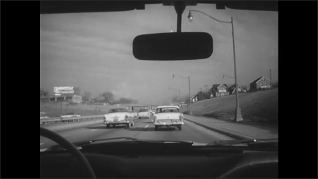 1960s: Hands move from steering wheel to turn signal. Car signal light blinks. Car changes lane on crowded expressway.