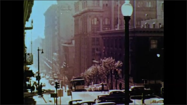 1960s: Tree branch, city buildings, downtown street, trolley travels down hill. Pedestrians cross street at crosswalk, walk down crowded sidewalk. Cars pass at intersection.
