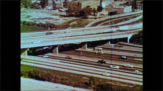 1960s: City buildings. Multiple lane highway, complex series of overpasses, cars drive.
