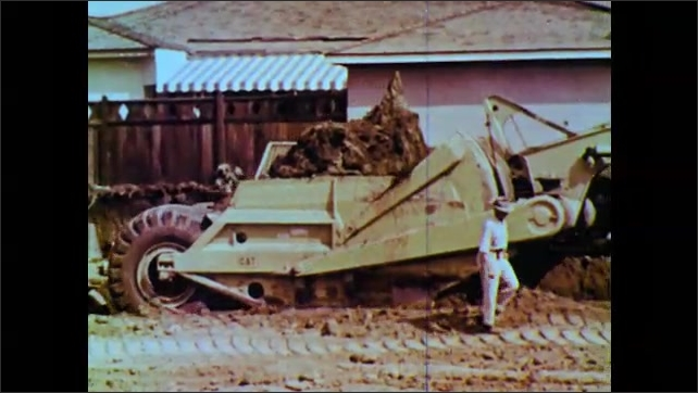 1960s: Earth moving machine deposits dirt, man walks along tire tracks in bare ground. Men operate heavy machinery.