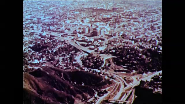 1960s: Steep mountains, roads, city, dense buildings, surface parking lots, cars.