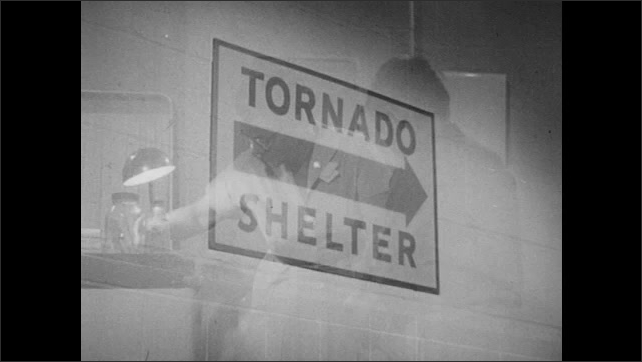 1960s: Storm clouds roll across sky. Sign for tornado shelter. Nurse cleans wound on boy's knee. Boy looks up.