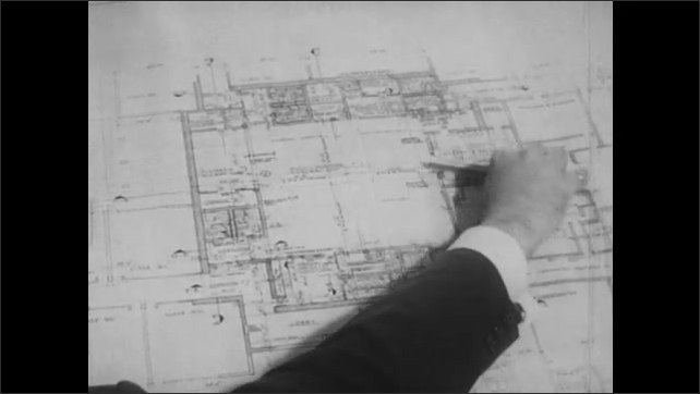 1960s: Scale model of school and grounds on table. Men talk and point to blueprints on table. Hands with pencils point to blueprint on table.