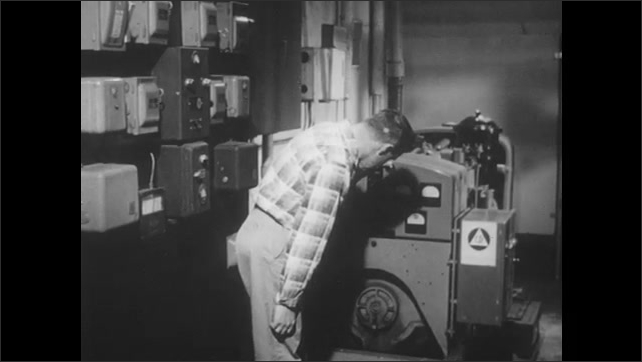 1960s: Man inspects and adjusts emergency electrical generator. Vent and air duct on ceiling.