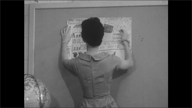 1960s: Woman speaks to boy. Boy smiles and returns to seat. Teacher hangs poster on bulletin board. Handmade emergency preparedness posters.