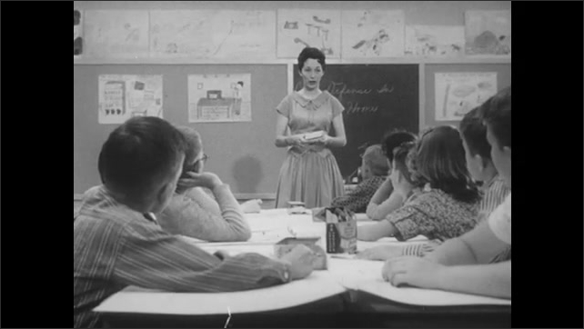 1960s: Teacher holds box and talks to children in classroom. Children sit at arts table and listen to teacher.