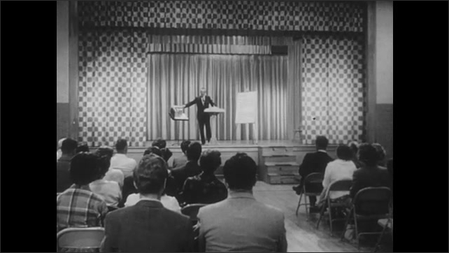 1960s: Man speaks into microphone at lectern. Hand points to model of fallout shelter. Man gives presentation on civil defense to audience in auditorium.