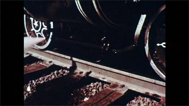 1950s: Steam blows from wheels of train on tracks then wheels begin moving. Smoke from locomotive fills sky. Large white house with columns. Hands picking cotton.