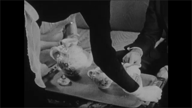 1930s: Woman holds out plate of cookies for people seated around coffee table to take. Each person takes a cookie.