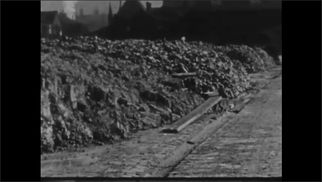 1930s: Rocks and dirt lay in excavated piles. Rocks are stacked.