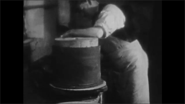 1930s: Man forms clay around mold. Man loads clay pitchers into saggar. Man sprinkles sand over container.