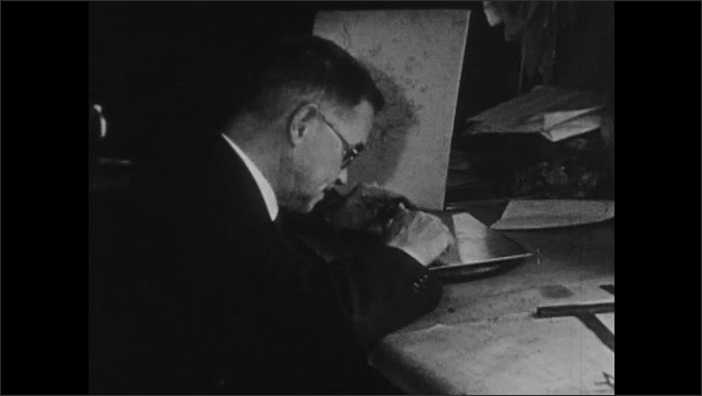 1930s: Man engraves metal plate, holds up plate.