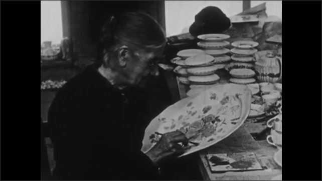 1930s: Woman sits at table, holds platter, paints on platter.