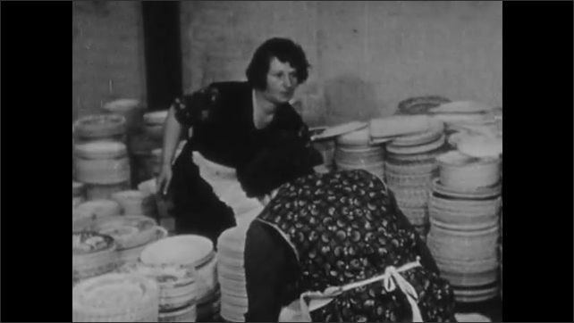 1930s: Women inspect stacks of plates.
