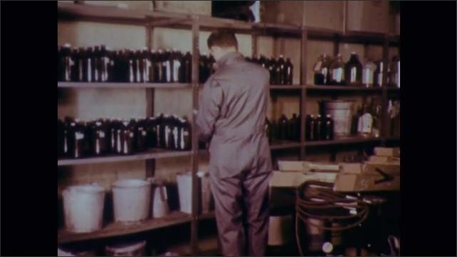 1970s: Shelves with bottles and buckets. Man moves bottle on shelf. Man pushes cart full of bottles.