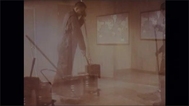 1970s: Man mops floor. Man squeezes out mop in bucket.