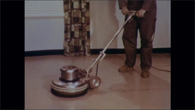 1970s: Man clean floor with electric scrubbing machine.