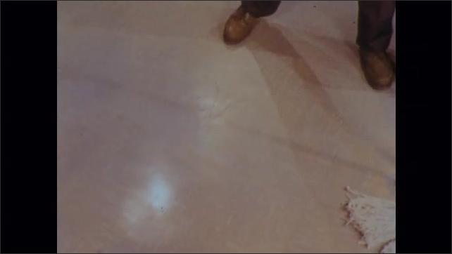 1970s: Man mops floor.