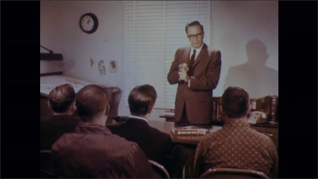1970s: Two men talk. Man stands at front of room, talks to to group of men seated in chairs.