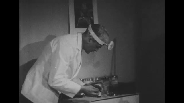 1950s: UNITED STATES: doctor applies antiseptic to agar plate.  Doctor places plate in oven.