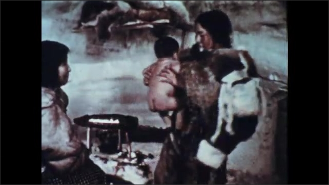 1950s: Wind blows across snow field. Two women in furs wrap baby in furs. Man stands watching, nods.