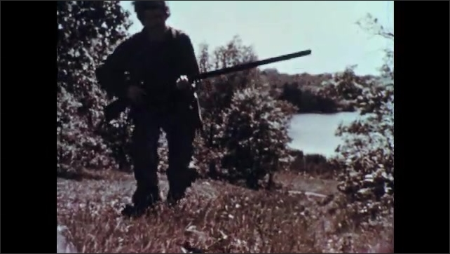 1950s: Man in coon-skin cap walks through woods carrying musket. Deer grazing in field. Man approaches and takes aim with gun. Deer looks up. Man fires gun. Deer go running.