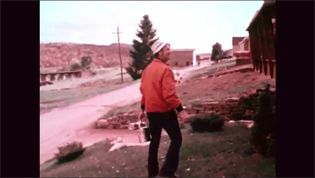 1970s: Man carries a tin lunch pail from house to a car. Man waves good-bye to family leaning out of windows, carrying a lunch pail and a thermos. Man waves and drives down street with suburban homes.