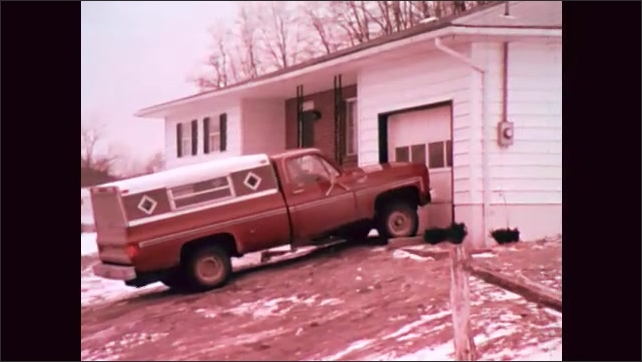 1970s: Mother lays little girl down for a nap. Pick-up truck drives up to house. Bearded Father pulls a toddler girl into his lap and gives her a bottle.