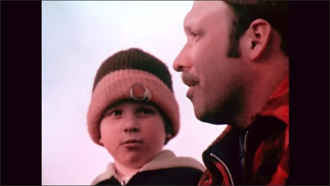 1970s: A man in a checked wool jacket talks to a boy in parkas and wool hats on top of a hill, explaining about a nest and coal mines.