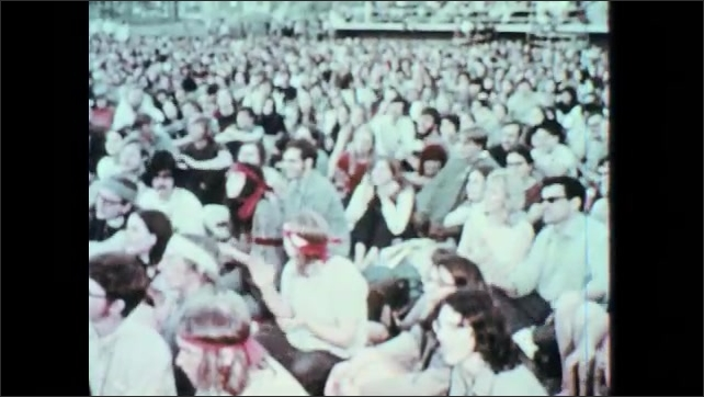 1960s: Images of riots. High tension situation. Large crowd sits and claps.